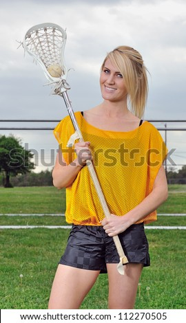Attractive young blonde female lacrosse player holds the ball in her lacrosse stick - smiling - stock photo