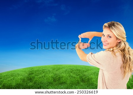 Attractive young blonde framing with her hands against green hill under blue sky - stock photo