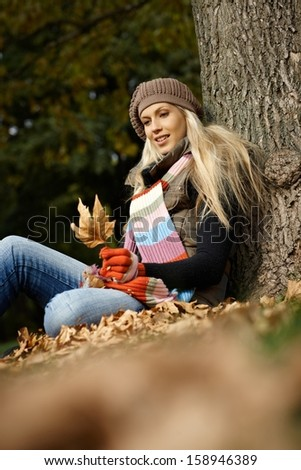Attractive young blonde girl sitting on ground in autumn park.