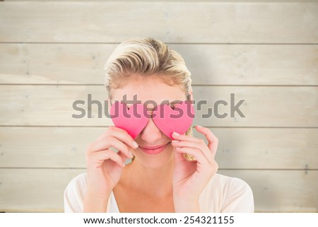 Attractive young blonde holding hearts over eyes against bleached wooden planks background - stock photo
