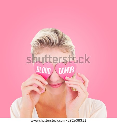 Attractive young blonde holding hearts over eyes against pink - stock photo