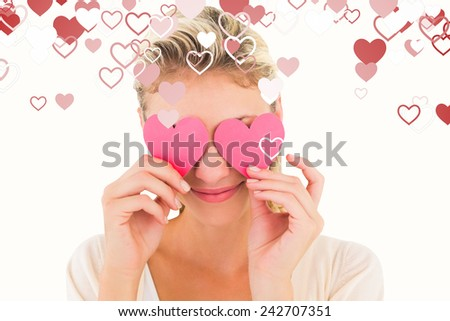 Attractive young blonde holding hearts over eyes against valentines heart design - stock photo