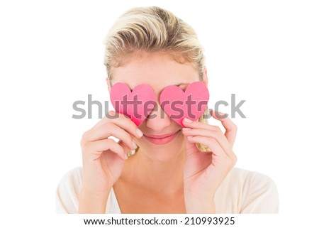 Attractive young blonde holding hearts over eyes on white background - stock photo
