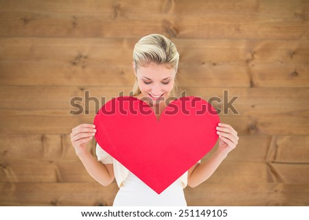 Attractive young blonde showing red heart against bleached wooden planks background - stock photo