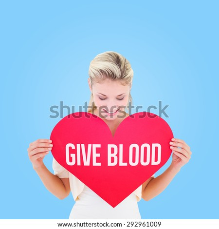 Attractive young blonde showing red heart against blue vignette background - stock photo