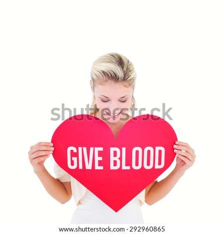 Attractive young blonde showing red heart against give blood - stock photo