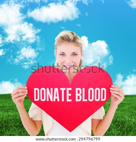 Attractive young blonde showing red heart against green field under blue sky - stock photo