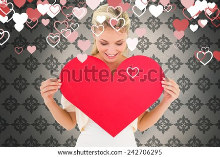 Attractive young blonde showing red heart against grey wallpaper - stock photo