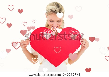 Attractive young blonde showing red heart against valentines heart design - stock photo