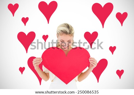 Attractive young blonde showing red heart against white background with vignette - stock photo
