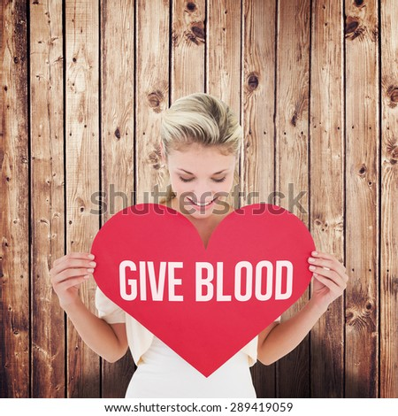 Attractive young blonde showing red heart against wooden planks - stock photo