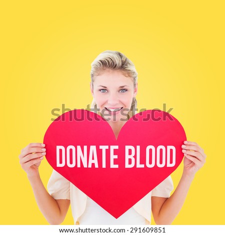 Attractive young blonde showing red heart against yellow vignette - stock photo