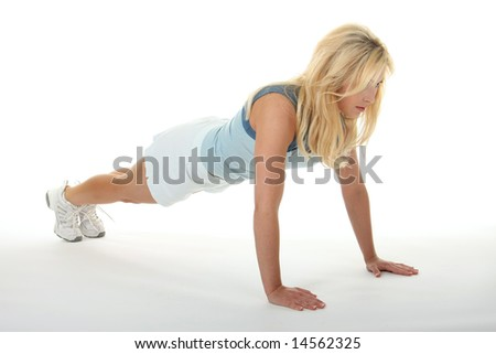 Attractive young blonde woman doing pushups, exercising, and working out. - stock photo
