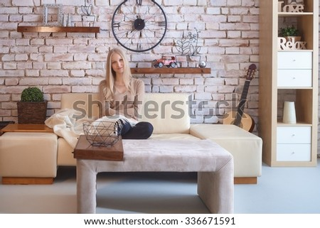 Attractive young blonde woman sitting on sofa at retro home, smiling, looking at camera. - stock photo