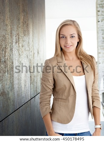 Attractive young blonde woman smiling, looking at camera, standing by metal wall.