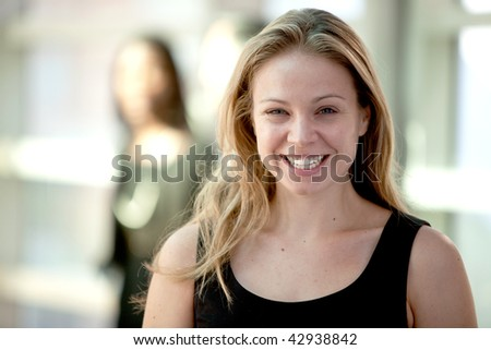 Attractive young blonde woman smiling while looking at camera with woman in background. Horizontally framed shot. - stock photo