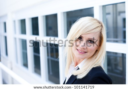 Attractive young blonde woman standing in front of a white framed window facade which gives the image strong architectural perspective - stock photo