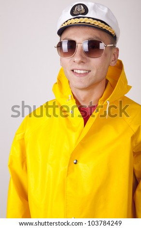 Attractive young boat captain with rain coat. - stock photo