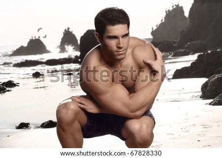 Attractive young body builder posing at the beach - stock photo