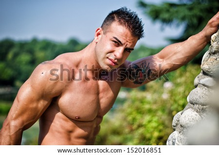 Attractive young bodybuilder outdoors, leaning against stone wall - stock photo