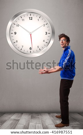 Attractive young boy holding a huge clock - stock photo