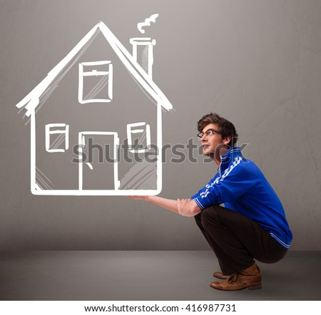 Attractive young boy holding a huge drawn house - stock photo