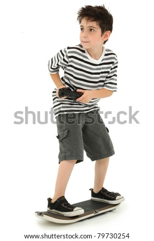 Attractive young boy on video game skateboard with joystick controller playing over white background. - stock photo