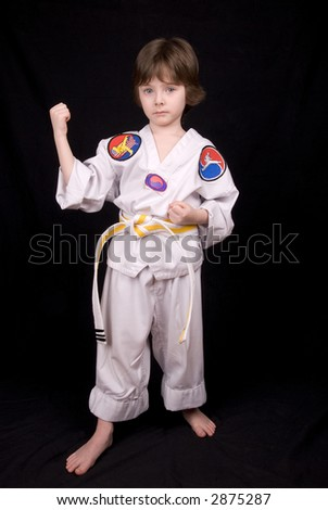 Attractive young boy Wearing Karate Outfit over a black background - stock photo