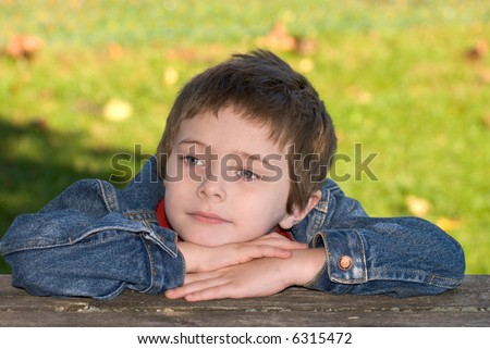 attractive young boy with head over his arms on a wood table - stock photo