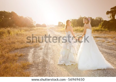 Attractive young bride and bridesmaid in formal attire looking over their shoulders at the camera.  They are walking on a country road. Horizontal shot. - stock photo