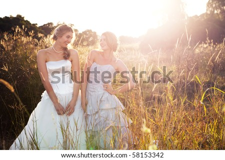 Attractive young bride and bridesmaid in formal attire. They are walking in the country holding hands at sunset. - stock photo
