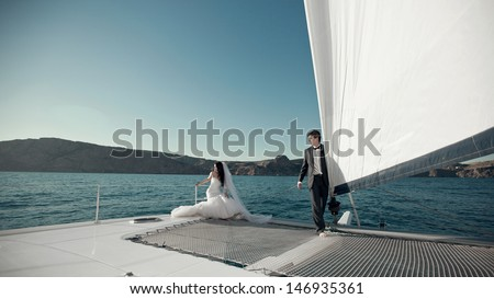 Attractive young bride and groom in wedding dress relaxing  on a deck yacht at a summer day  - stock photo