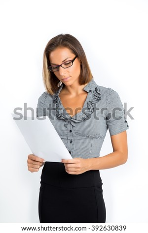 Attractive, young brunette business woman wearing glasses, reading documents. Isolated on white background