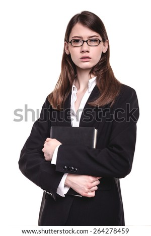 Attractive young brunette businesswoman standing with her arms crossed - stock photo