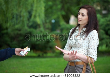attractive young brunette female refuse to take cigarette from friend, park shoot - stock photo