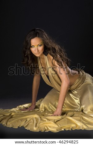 Attractive young brunette girl in a beautiful gold dress - stock photo