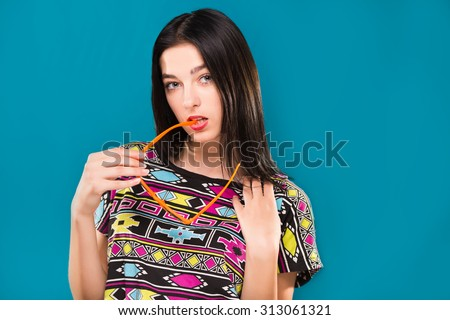 Attractive young brunette girl, with straight hair, wearing in colorful shirt, posing with sunglasses in her hand, on the blue background, in studio, waist up - stock photo