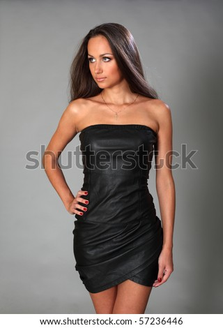 Attractive young brunette in a cocktail dress - stock photo