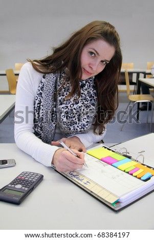 Attractive young Brunette in English class taking notes - stock photo