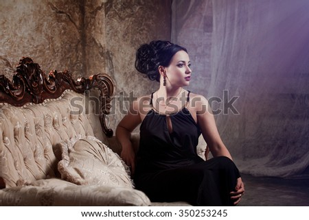 attractive young brunette in stylish black evening dress, is back  half a turn, sitting on the sofa - stock photo