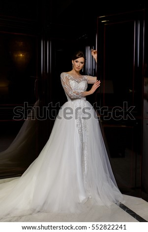Attractive young brunette model poses in long bridal dress with lace on fashion background