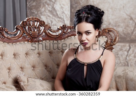 attractive young brunette sitting on  beautiful sofa, portrait close-up, gold eyeshadow - stock photo
