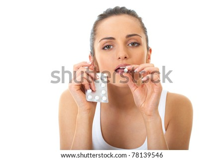 attractive young brunette takes some pills, isolated on white