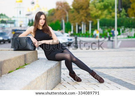 Attractive young brunette wearing black dress posing near the road - stock photo
