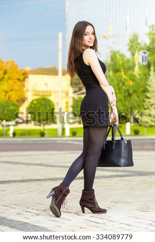 Attractive young brunette wearing black dress posing with handbag - stock photo