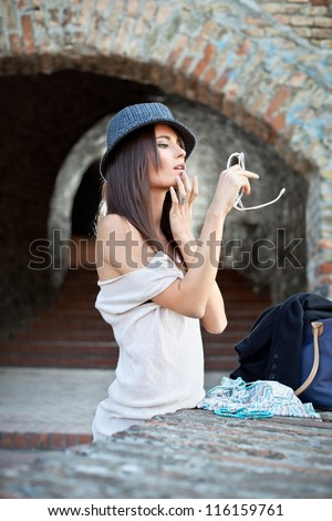 Attractive young brunette  with hat posing. Fashion concept. - stock photo