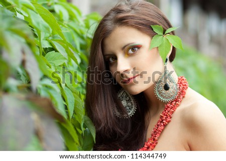 attractive young brunette with unusual make up looking into the camera - stock photo