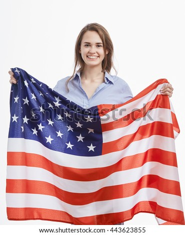 Attractive young brunette woman holding National Flag celebrating Independence Day on 4th of July in United States of America.Cute model with toothy smile on isolated white background - stock photo