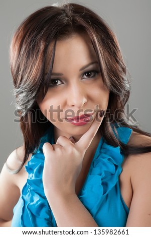 Attractive young brunette woman in a blue dress