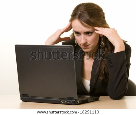 Attractive young brunette woman in business suit leaning on hands sitting at a desk looking bored or depressed